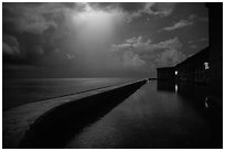 Fort Jefferson seawall at night with sky lit by thunderstorm. Dry Tortugas National Park, Florida, USA. (black and white)