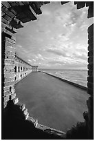 Fort Jefferson seawall and moat, framed by a crumpling embrasures, late afternoon. Dry Tortugas National Park, Florida, USA. (black and white)