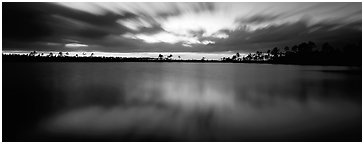 Dark clouds in motion at sunset over lake. Everglades National Park (Panoramic black and white)