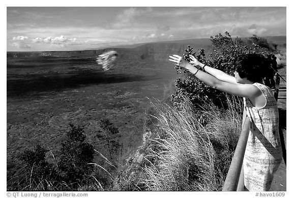Woman throws flowers into Kilauea caldera as offering to Pele. Hawaii Volcanoes National Park (black and white)