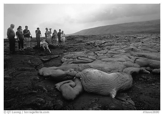 Hikers observe a live lava flow at close distance. Hawaii Volcanoes National Park (black and white)