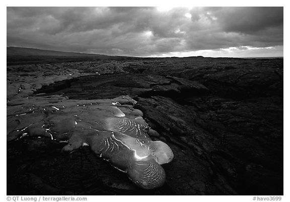 Flowing lava and rain clouds at dawn. Hawaii Volcanoes National Park (black and white)