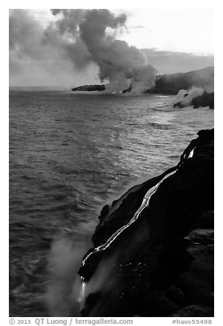 Bright molten lava flows into the Pacific Ocean, plume in background. Hawaii Volcanoes National Park (black and white)