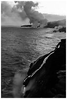 Bright molten lava flows into the Pacific Ocean, plume in background. Hawaii Volcanoes National Park, Hawaii, USA. (black and white)