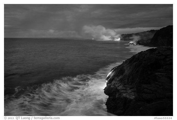 Streams of hot lava flow into the Pacific Ocean at the shore of erupting Kilauea volcano. Hawaii Volcanoes National Park (black and white)