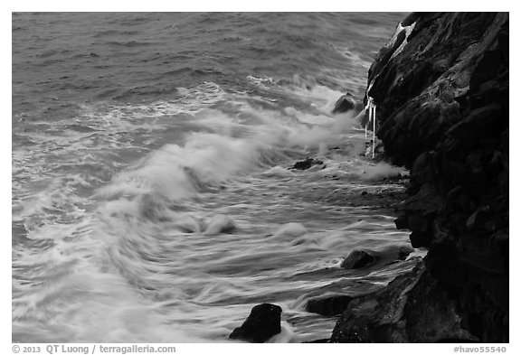 Waves and hot lava dripping from lava bench. Hawaii Volcanoes National Park (black and white)