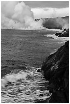 Coast with lava and clouds of smoke and steam produced by lava contact with ocean. Hawaii Volcanoes National Park, Hawaii, USA. (black and white)