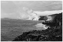 Hiker and volcanic steam cloud on coast. Hawaii Volcanoes National Park, Hawaii, USA. (black and white)