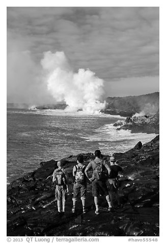 Hikers looking at molten lava and coastal volcanic steam cloud. Hawaii Volcanoes National Park (black and white)