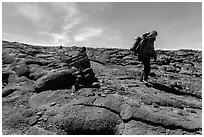 Hiker descending from Mauna Loa summit next to sign. Hawaii Volcanoes National Park, Hawaii, USA. (black and white)