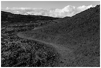 Trail through olivine hill bordering aa lava. Hawaii Volcanoes National Park, Hawaii, USA. (black and white)