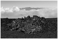 Black of colorful lava on Mauna Loa, Mauna Kea emerging from Saddle clouds. Hawaii Volcanoes National Park ( black and white)
