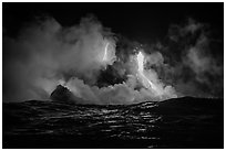 Lava cascades lighting ocean at night. Hawaii Volcanoes National Park, Hawaii, USA. (black and white)