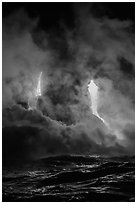 Lava cascading cliffs above ocean waves at night. Hawaii Volcanoes National Park, Hawaii, USA. (black and white)