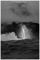 A single spigot of lava creates a large plume steam at sunrise upon reaching ocean. Hawaii Volcanoes National Park, Hawaii, USA. (black and white)