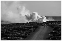 Byciclists and hikers approaching lava ocean entry on emergency road. Hawaii Volcanoes National Park ( black and white)