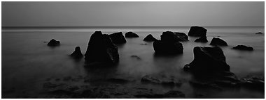 Seascape with boulders in water at dusk. National Park of American Samoa (Panoramic black and white)