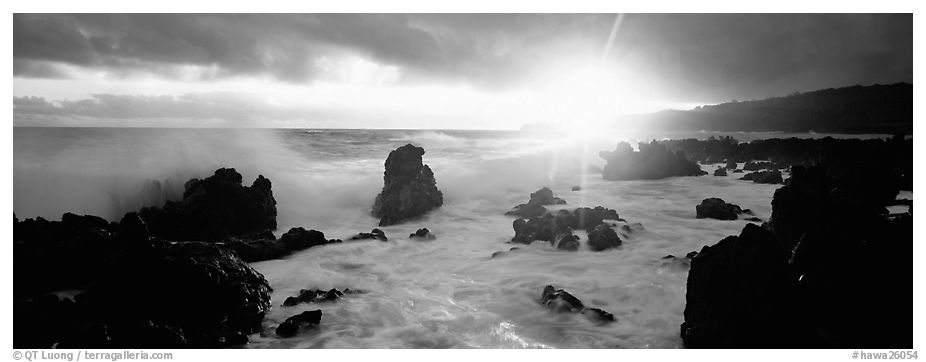 Primeval seascape with surf and rising sun. Maui, Hawaii, USA (black and white)