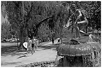 Young men carring surfboards next to statue of surfer, Kapiolani Park. Waikiki, Honolulu, Oahu island, Hawaii, USA ( black and white)