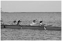 Young women padding a hawaiian outrigger canoe, Maunalua Bay, late afternoon. Oahu island, Hawaii, USA (black and white)