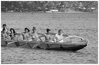 Outrigger canoe paddled by women in bikini, Maunalua Bay, late afternoon. Oahu island, Hawaii, USA (black and white)