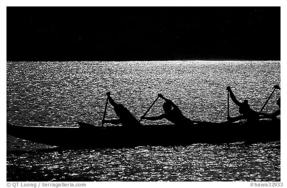 Backlit hawaiian canoe paddlers, Maunalua Bay, late afternoon. Oahu island, Hawaii, USA