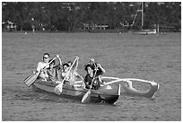 Boys paddling an outrigger canoe, Maunalua Bay, late afternoon. Oahu island, Hawaii, USA (black and white)