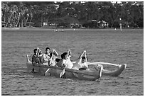 Girls paddling an outrigger canoe, Maunalua Bay, late afternoon. Oahu island, Hawaii, USA (black and white)