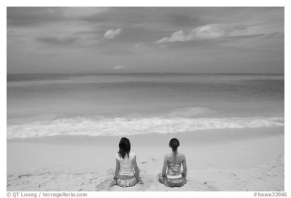 Young women facing ocean in meditative pose on Waimanalo Beach. Oahu island, Hawaii, USA (black and white)