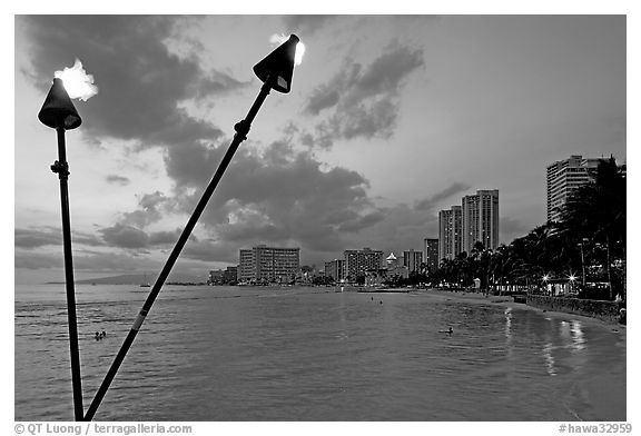Bare flame torches and skyline at sunset. Waikiki, Honolulu, Oahu island, Hawaii, USA (black and white)