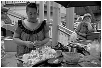 Woman preparing a fresh flower lei, with another woman looking, International Marketplace. Waikiki, Honolulu, Oahu island, Hawaii, USA (black and white)