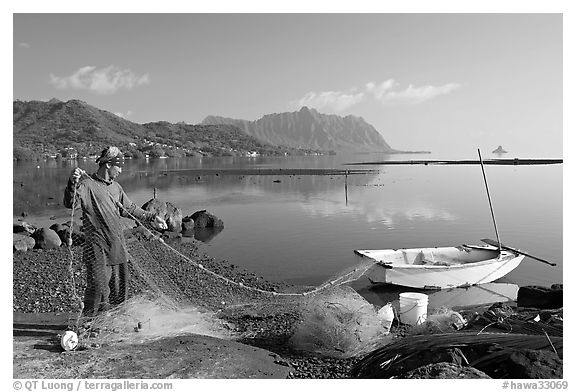 Fisherman pulling out net out of small baot, Kaneohe Bay, morning. Oahu island, Hawaii, USA (black and white)