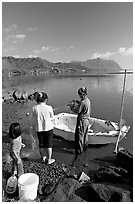 Fisherman and family pulling out net out of small baot, Kaneohe Bay, morning. Oahu island, Hawaii, USA (black and white)