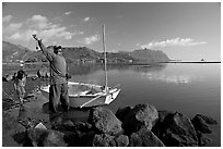 Fisherman pulling out fish out a net, with girl looking, Kaneohe Bay, morning. Oahu island, Hawaii, USA (black and white)