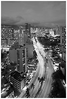 Boulevard and high rise buildings at dusk. Waikiki, Honolulu, Oahu island, Hawaii, USA ( black and white)