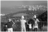 Tourists look at Waikidi from the  Diamond Head crater, early morning. Oahu island, Hawaii, USA (black and white)