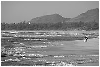 Woman with child on beach, Lydgate Park, early morning. Kauai island, Hawaii, USA ( black and white)