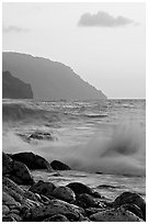 Boulders, waves, and Na Pali cliffs, sunset. Kauai island, Hawaii, USA ( black and white)
