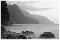 Boulders, surf, and Na Pali cliffs, sunset. Kauai island, Hawaii, USA ( black and white)