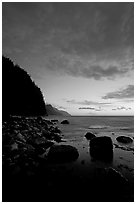 Boulders, surf, and Na Pali cliffs, dusk. North shore, Kauai island, Hawaii, USA (black and white)