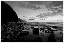 Boulders, surf, and Na Pali Coast, dusk. Kauai island, Hawaii, USA (black and white)