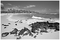Dark rocks and Kiahuna Beach, mid-day. Kauai island, Hawaii, USA (black and white)
