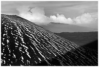 Cinder cone with snow stripes, distant clouds. Mauna Kea, Big Island, Hawaii, USA (black and white)