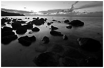 Boulders in water near Kalihika Park, sunset. Kauai island, Hawaii, USA (black and white)