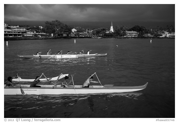 Outrigger canoes and town under storm sky, Kailua-Kona. Hawaii, USA (black and white)