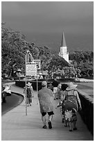 Beachgoers walking past ironman triathlon sign, Kailua-Kona. Hawaii, USA (black and white)