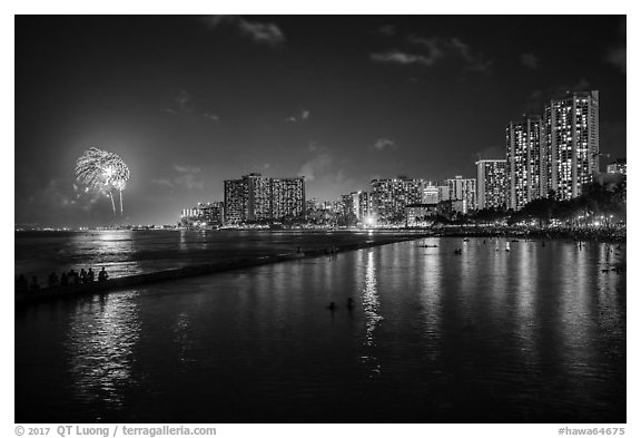 Watching fireworks from seawall, Kuhio Beach, Waikiki. Waikiki, Honolulu, Oahu island, Hawaii, USA (black and white)