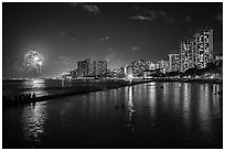 Watching fireworks from seawall, Kuhio Beach, Waikiki. Waikiki, Honolulu, Oahu island, Hawaii, USA ( black and white)