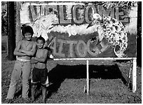 Children in front of a turtle a shark sign in Vaitogi. Tutuila, American Samoa ( black and white)