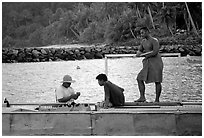 Men on a ferry to Aunuu. Aunuu Island, American Samoa ( black and white)